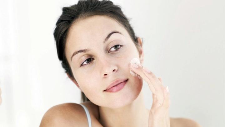 Lady applying face cream