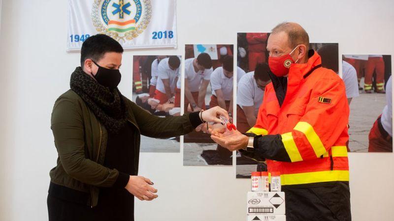 Unilever munkatársa Győrfi Pálnak ad a kezébe egy darabot a Lifebouy Total higiénikus kézgéljéből.
