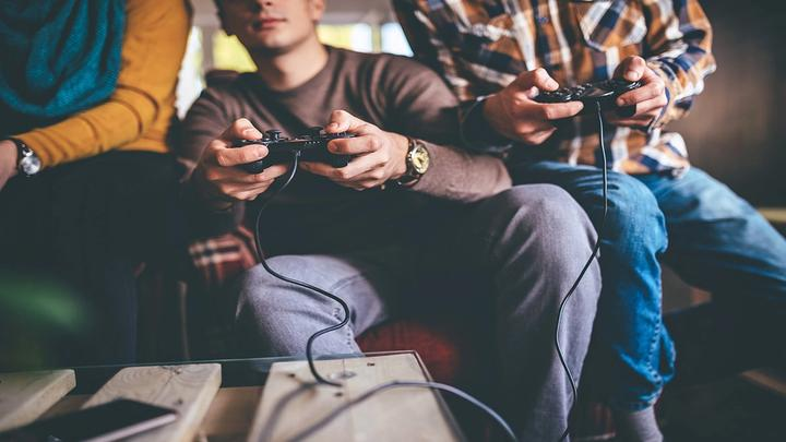 Photo focused in on the hands of three people sitting on a sofa using games consoles to play an online game