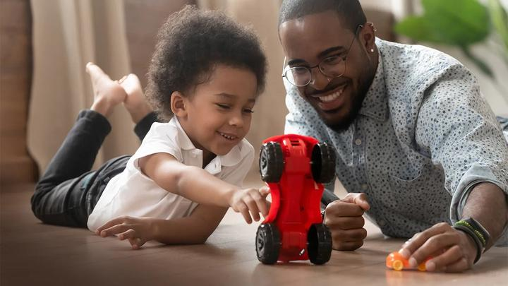 Boy and father playing with toy car