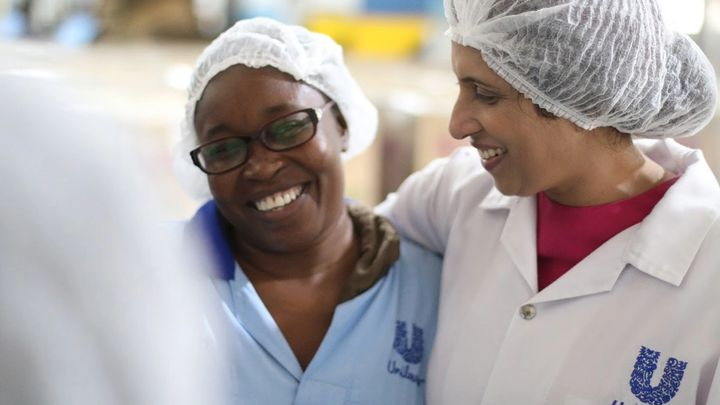 Two ladies in PPE and Unilever uniform with their arms around eachother smiling