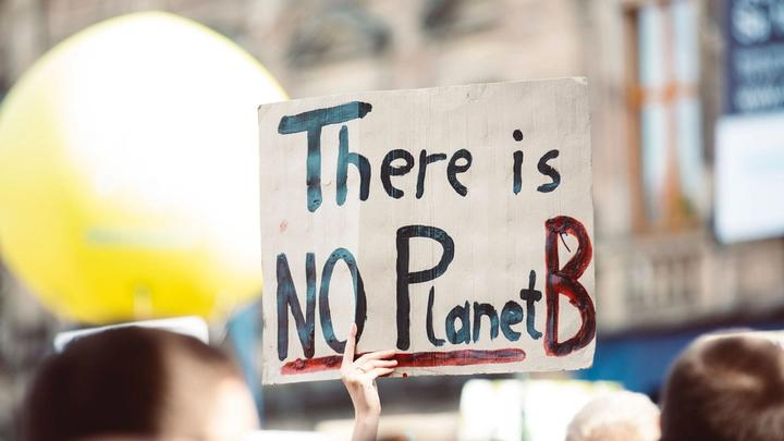 """Person holding up sign saying 'There is no Planet B"""""""