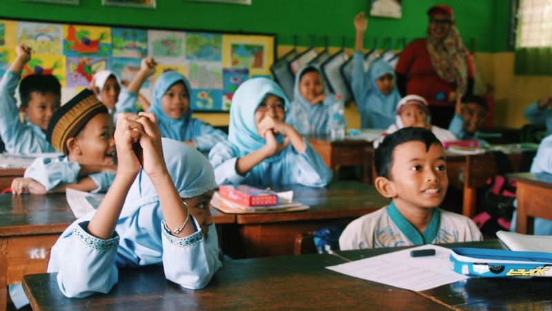 Children sitting in a classroom learn about handwashing
