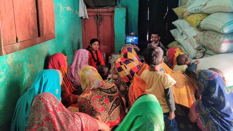 Women sit together watching an iPad as part of a local workshop