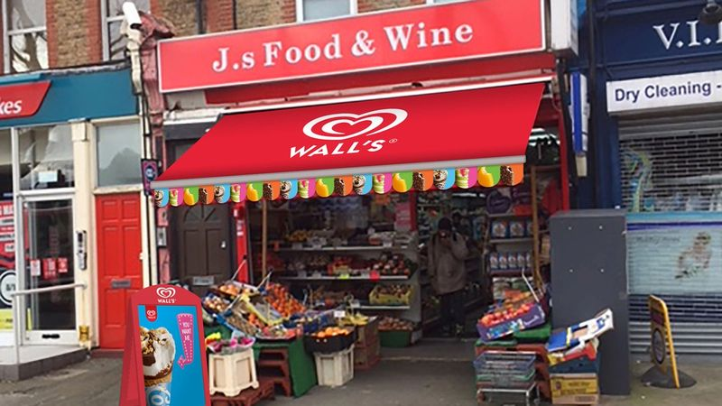 A small shop in the UK with fruit and vegetables displayed under a red Wall's ice cream awning