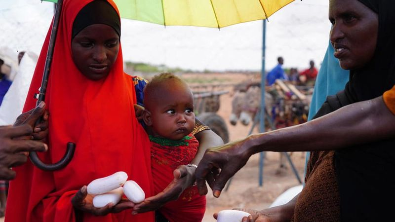 Woman with baby in Africa being handed bars of soap by volunteer