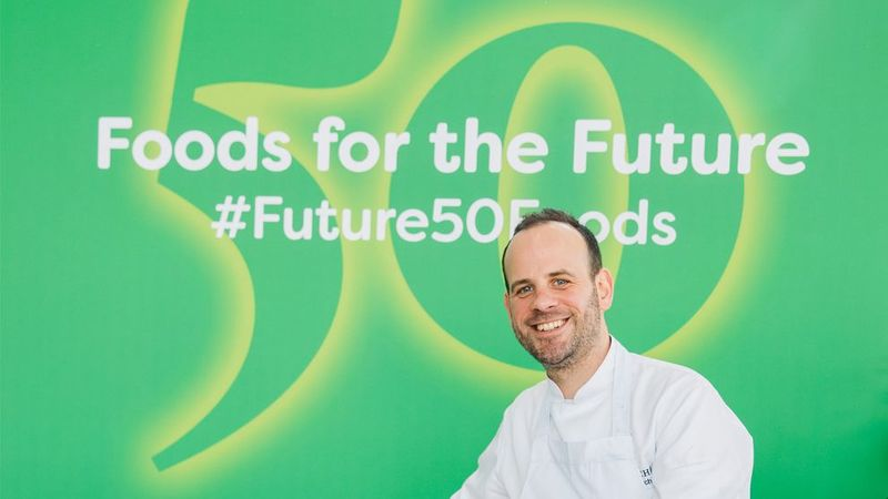 Michelin-starred chef Gregory Marchand sits in front of a green banner featuring the text Future 50 Foods
