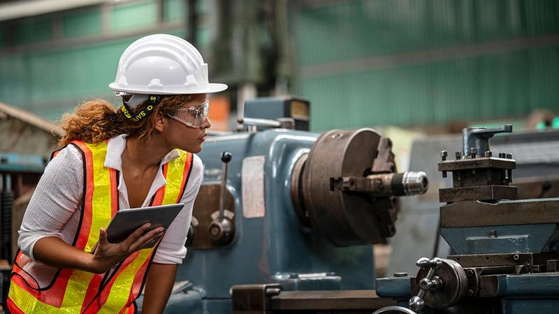 Factory worker assessing material