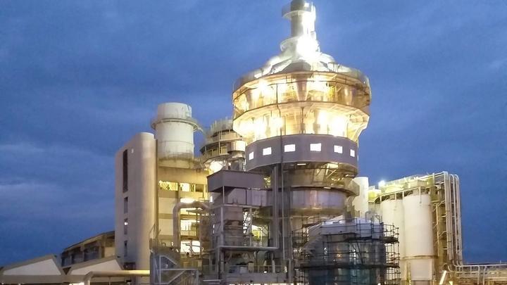 An illuminated factory tower against a dark blue night sky