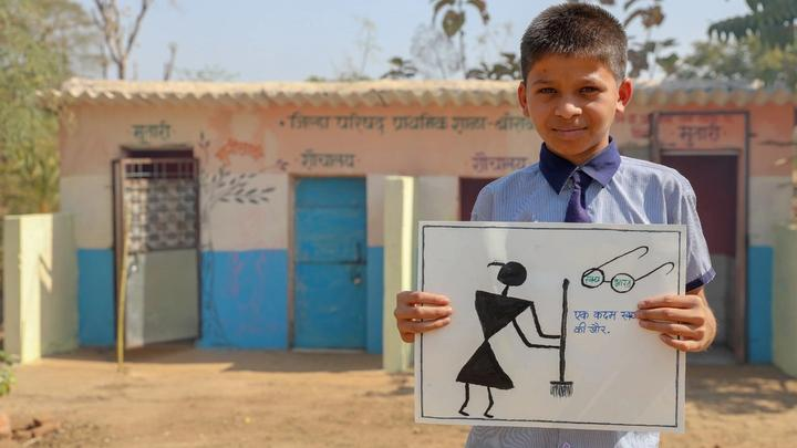 A schoolboy stands in front of a block of toilets holding a hand-drawn poster