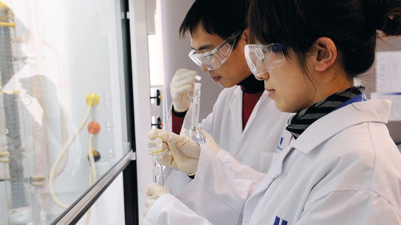 A woman and a man wearing Unilever lab coats looking into a fumehood in a lab