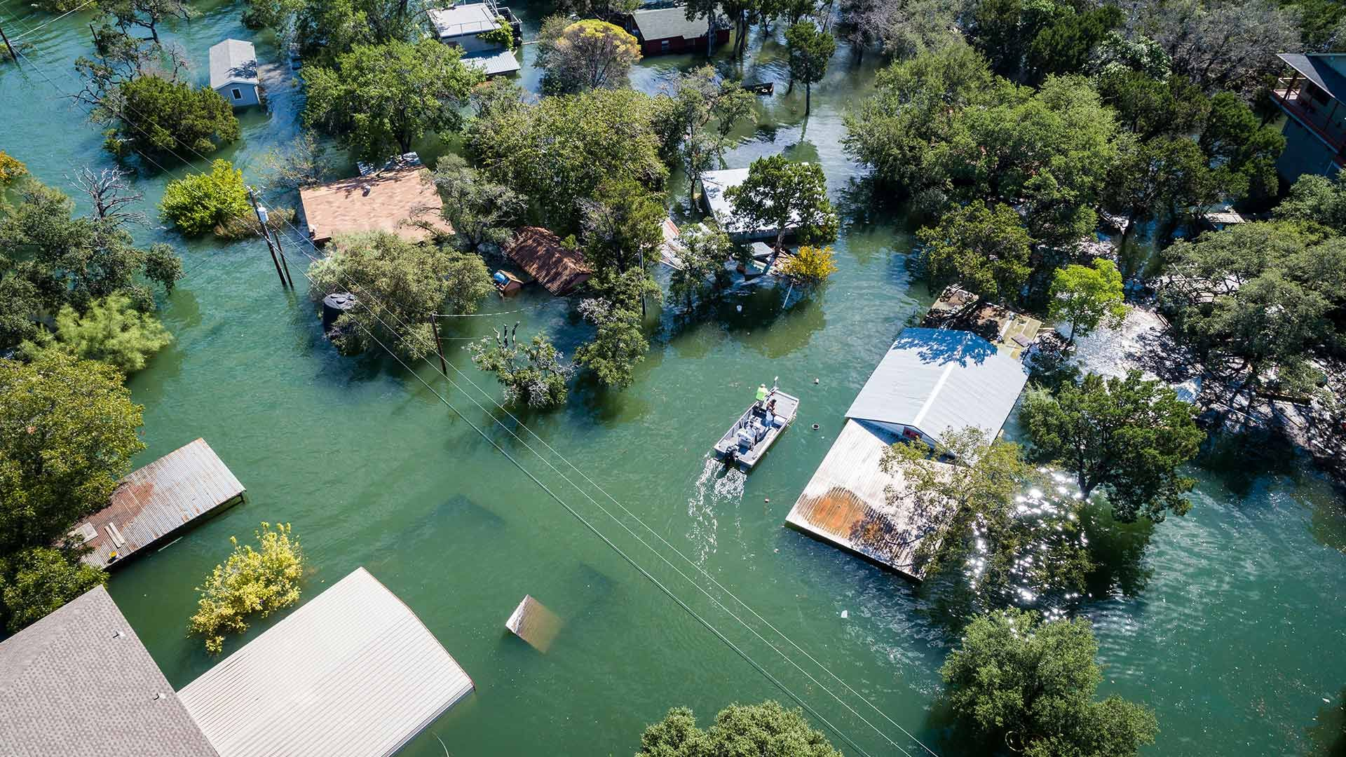 aerial view of flooded village in remote location with trees