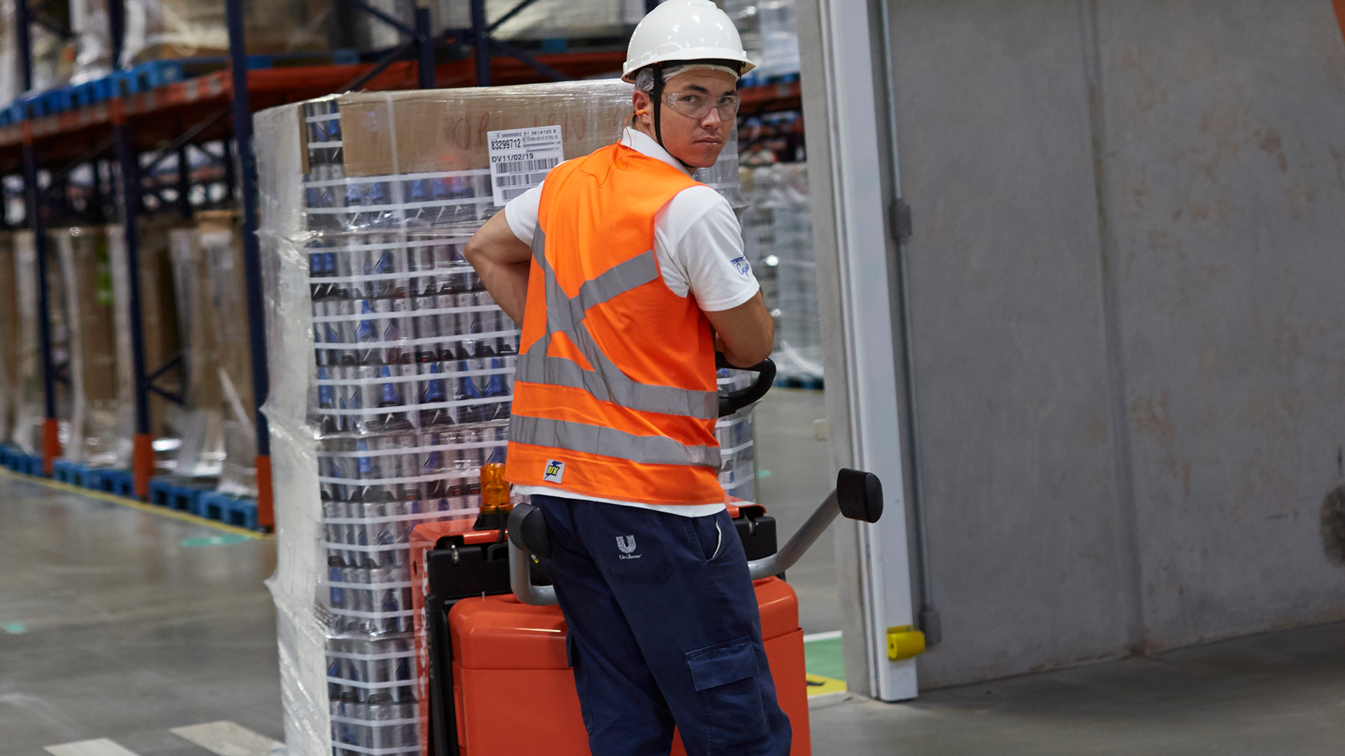 Worker in overalls and hard hat pulling a trolley across a factory floor