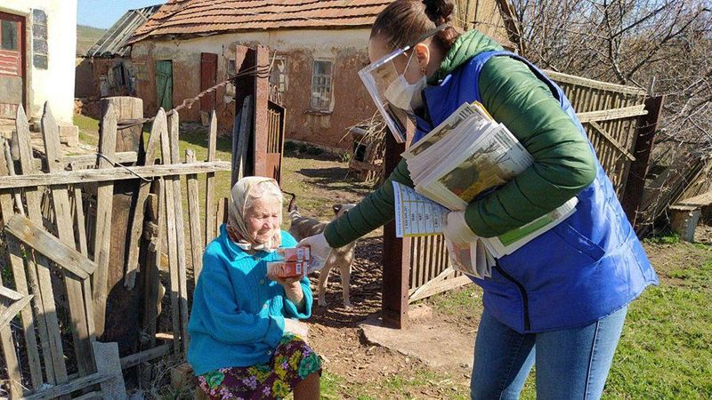 Elderly woman with headscarf receiving a Unilever product donation – part of Unilever's work with the UN Refugee Agency