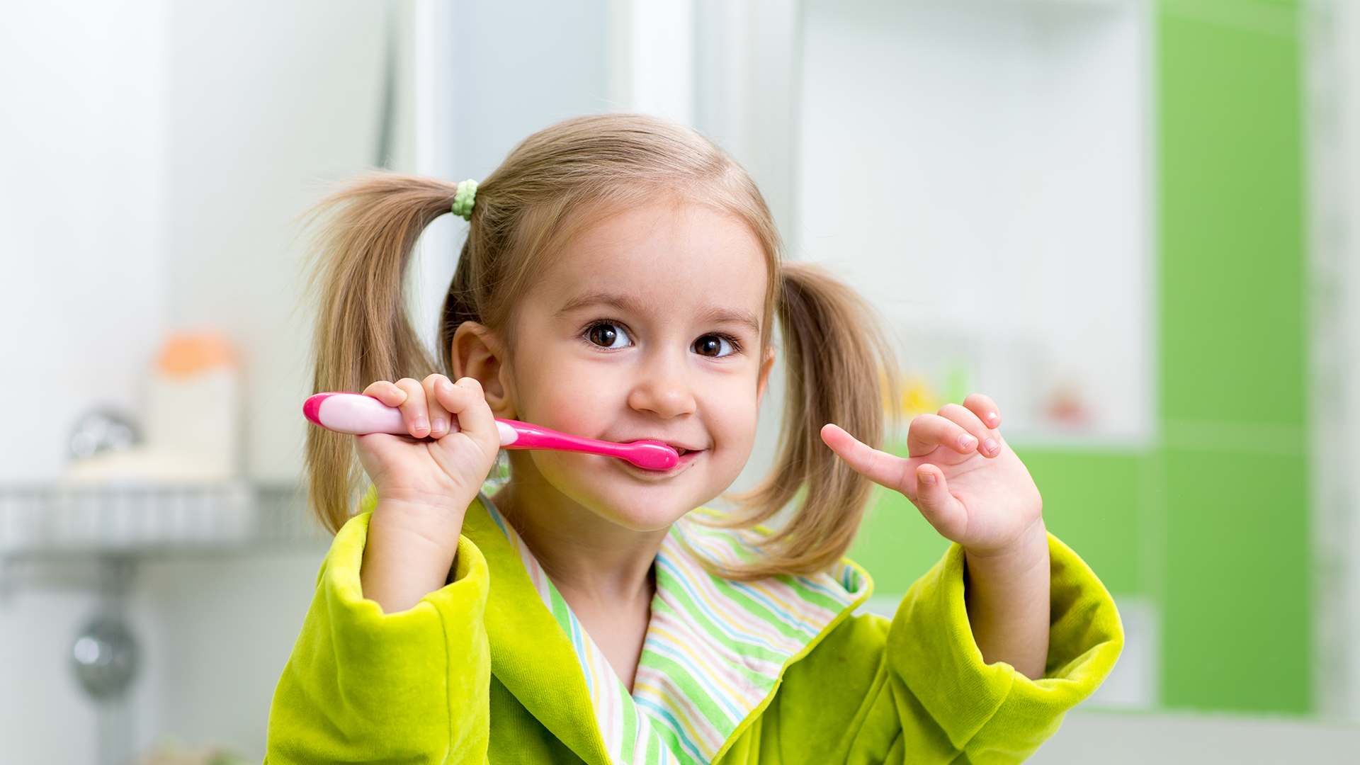 A young girl brushing her teeth and smiling
