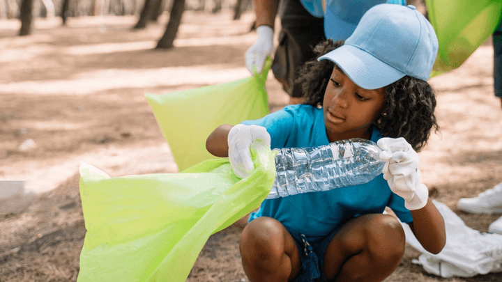 A child in a blue cap picking up plastic from a beach