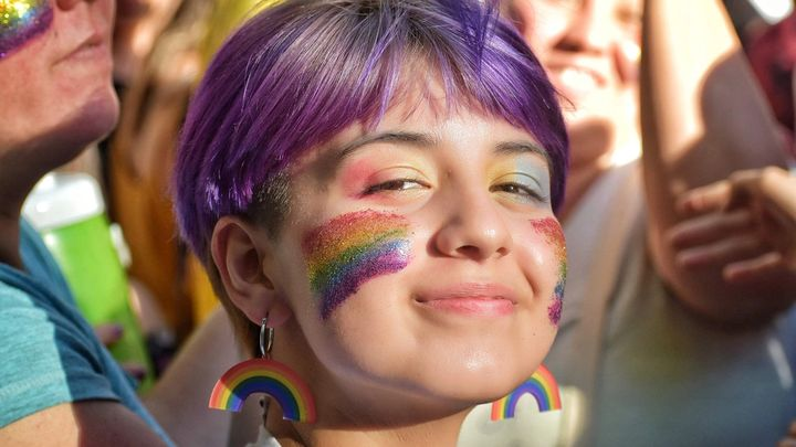A girl with purple hair smiling, with Pride flags painted on her face