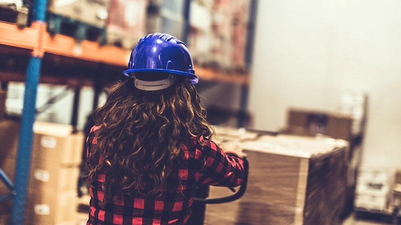 The back of the head of a young woman in a hard hat surveying a warehouse of goods