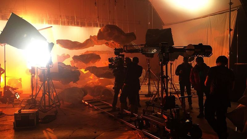 A film crew in a studio is setting up a shot of a large screen with floating grey and orange cut-out clouds.