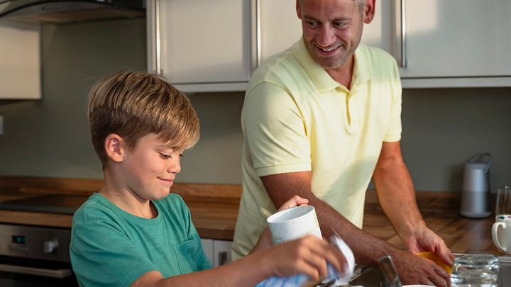Father and young son in a kitchen doing the washing up together