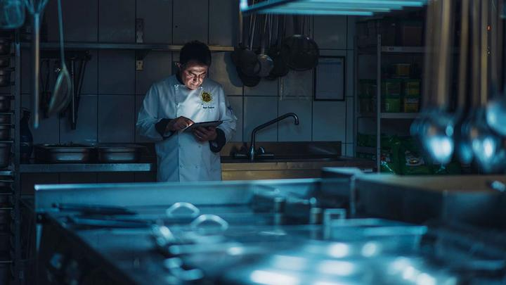 Chef in the dark looking at iPad. Unilever Food Solutions is working to help food operators cope with Covid-19