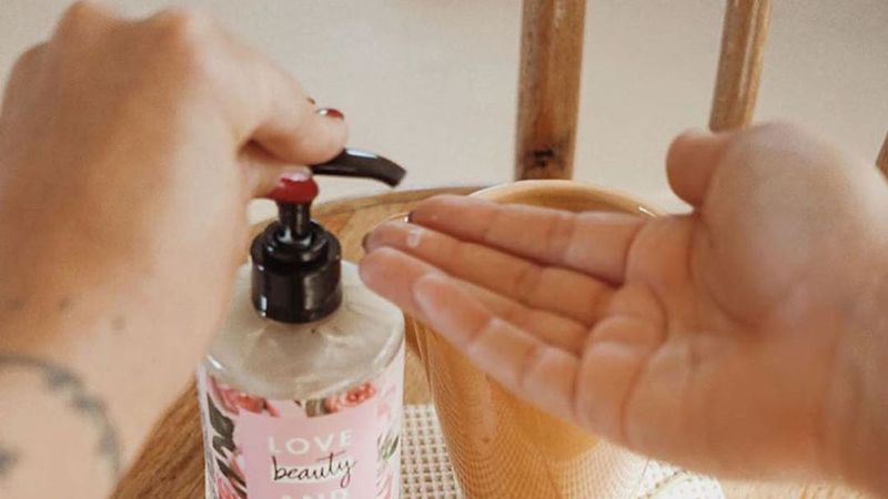 A person using Love Beauty and Planet body lotion