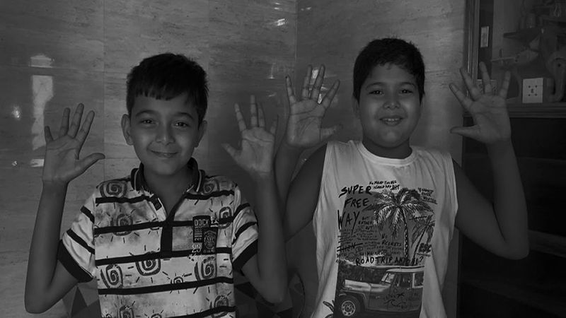 Two young boys showing their clean hands in India