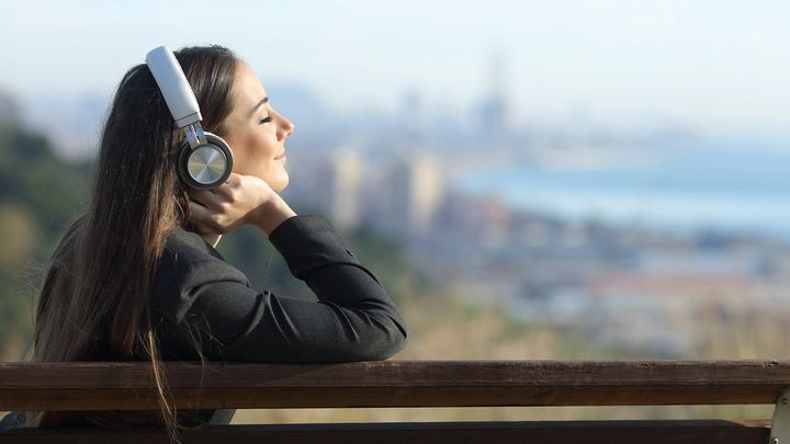 A woman with headphones sitting on bench overlooking a city in the distance
