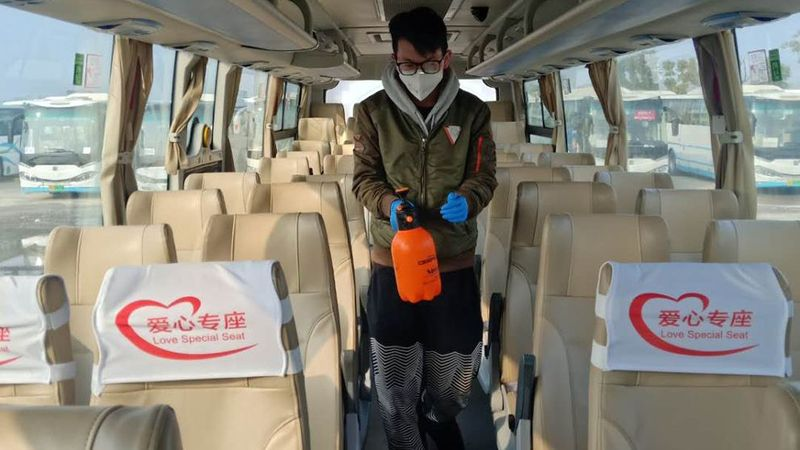 A man walks down the aisle of a bus with cleaning equipment
