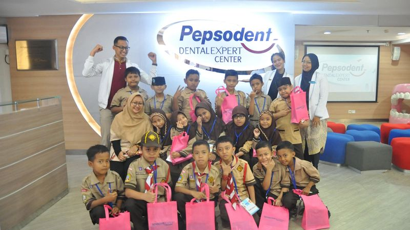 Children and dentists posed in a group in the Pepsodent Dental Expert Centre waiting room