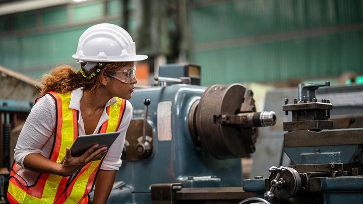 Factory worker assessing a machine