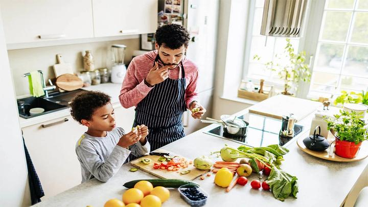 Man and young boy preparing, chopping and snacking on vegetables