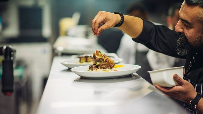 Chef adding final touches to plate of food