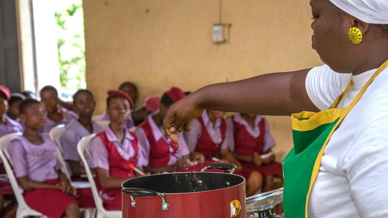 A demonstrator shows a class of schoolgirls in Nigeria how to improve their diet