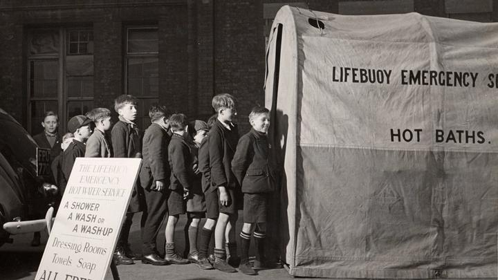 A photograph of young boys queuing for Lifebuoy's public aid emergency washing service during the Blitz in World War 2.