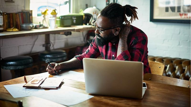 Man with beard working at laptop. Unilever Flex Experience matches people with projects that offer the chance to upskill.