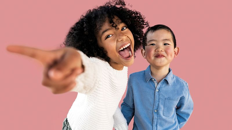 A young girl holding the hand of a younger boy points at the camera