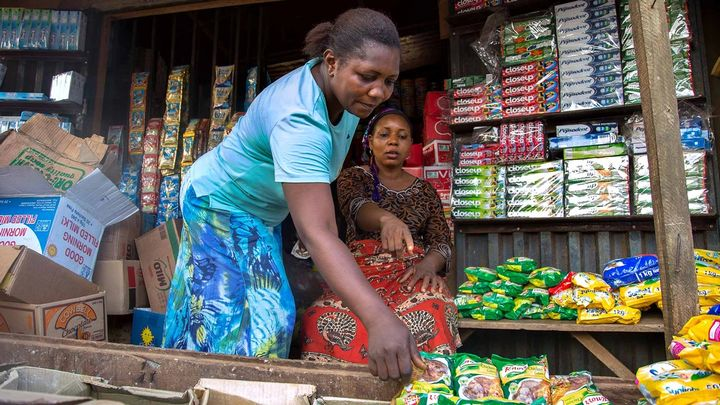 Two women working outside of a small shop