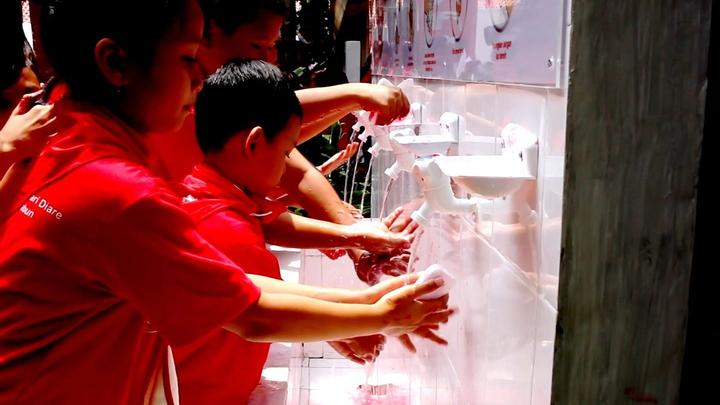 A group of children raise their hands whilst taking part of Lifebuoy's handwashing programme