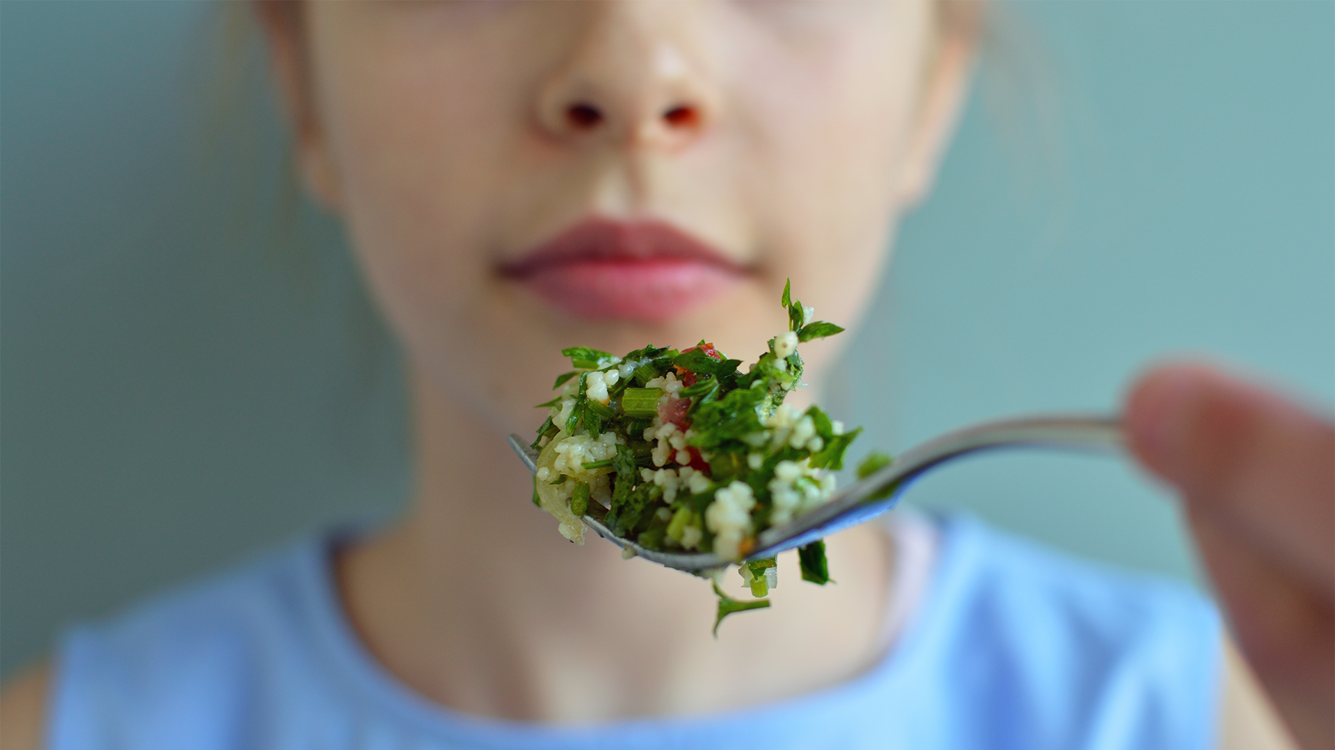 A young girl holding a spoon of salad in front of her