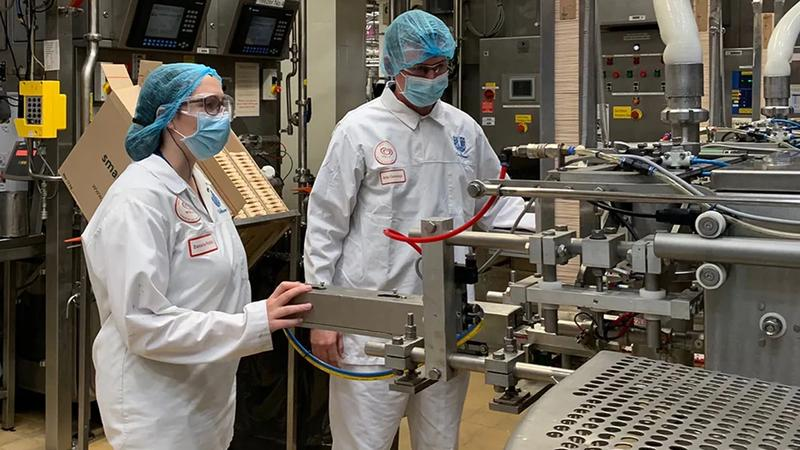 Man and women in hairnets and white coats on a factory floor checking machinery
