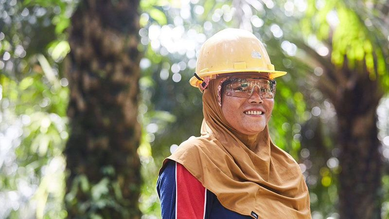 A woman in a headscarf and yellow hard hat stands in focus smiling with palm trees behind her