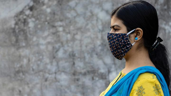 Side Face of an Indian woman wearing homemade cotton nose mask to reduce the spread of Covid-19 – stock photo
