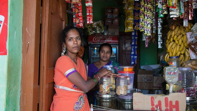 Two Shakti micro-entrepreneurs standing beside their small shop in India