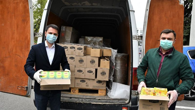 Unilever products, donated to a hospital, being unloaded from a van by two men wearing surgical masks