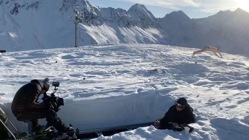On a sunny snow field surrounded by mountains  a photo crew ski wear is photographing a man doing press-ups in boxer shorts