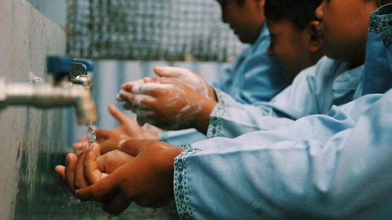 Three children washing their hands under a tap.