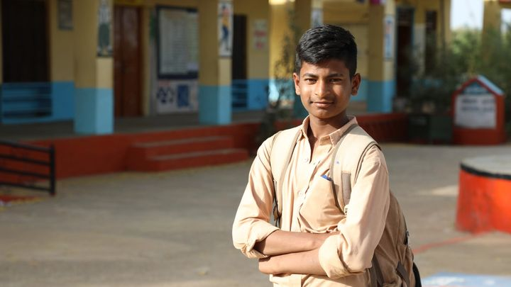 A young boy stands outside school toilets in India