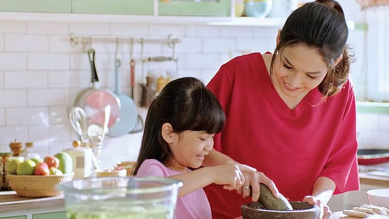 A mother and daughter cook together in a kitchen