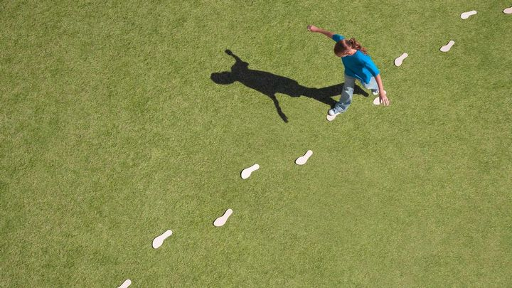 A young girl walking across a field whilst balancing on footstep outlines
